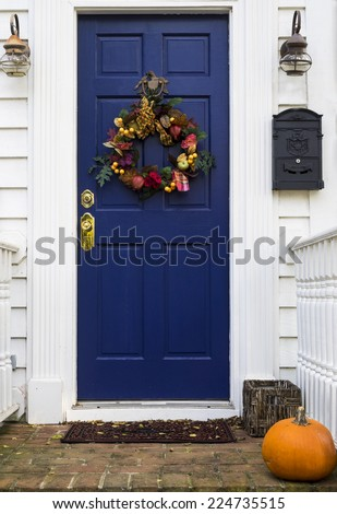 Blue door of house decorated with Autumn-themed wreath. - stock photo