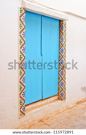 Blue door on a white wall, doorway with lovely tile decoration - stock photo