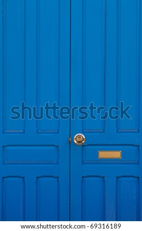 Blue door with golden bolt and golden tag. - stock photo