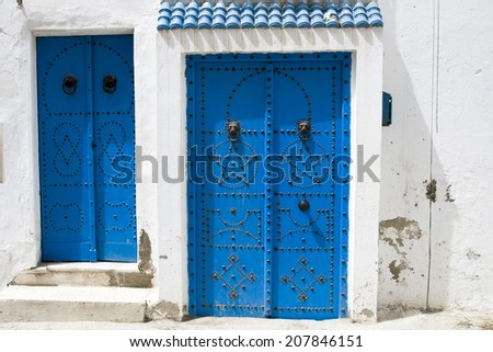 Blue doors, window and white wall of traditional building in Sidi Bou Said, Tunisia  - stock photo