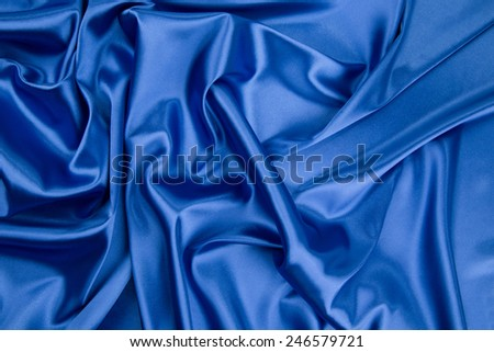 Blue drapery silk fabric. Located on a whole background. - stock photo