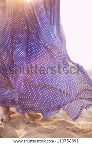blue dress developing on the wind. sunset - stock photo