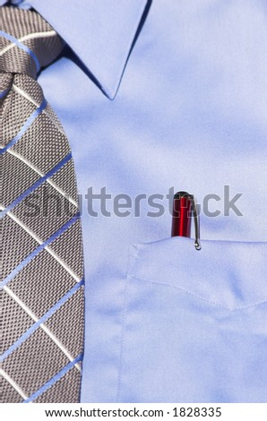 Blue dress shirt with striped tie and red pen in pocket