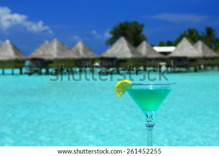 Blue drink with turquoise lagoon and huts in background in Bora Bora - stock photo