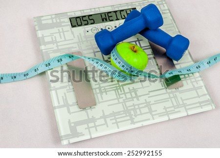 Blue dumbbells and apple and measure tape on weighing machine with sign loss weight - stock photo