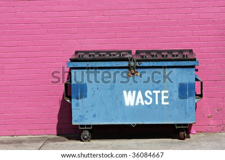Blue dumpster against a bright pink wall - stock photo
