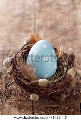 Blue easter egg in nest on wooden background - stock photo