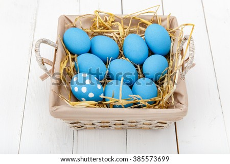 Blue easter eggs in a basket on a white wooden table - stock photo
