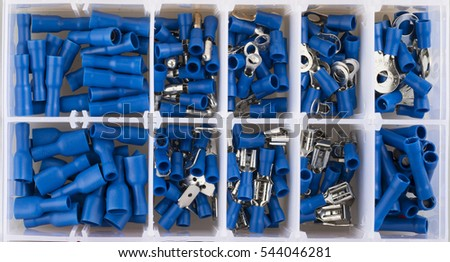 Blue electric terminal connectors organized in plastic container.
