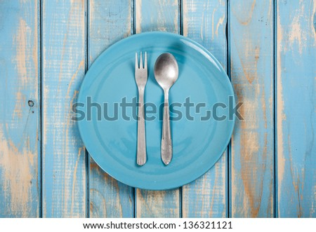 Blue empty plates with fork and spoon - stock photo