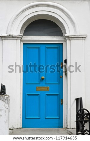 Blue entrance door on house with arch - stock photo