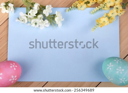 Blue envelope with decorated Easter eggs and flowers around border - stock photo