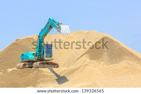 blue excavator extening its bucket at sandpit - stock photo