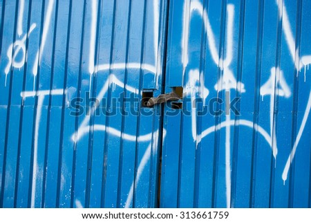 Blue external gate locked with white graffiti - stock photo