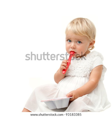 Blue eye baby girl sitting with red spoon and boring face expression . Isolated on white background. - stock photo