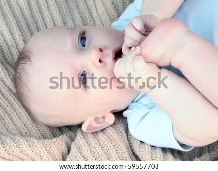 Blue eyed baby boy tasting his toes - stock photo