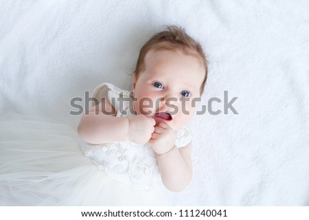 Blue eyed baby girl in a white dress - stock photo