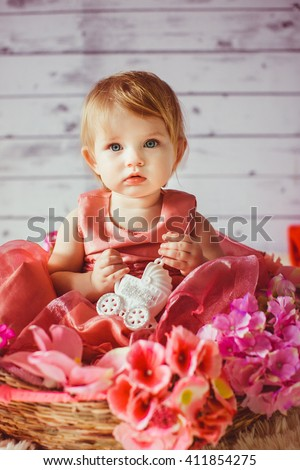 Blue eyed baby in the basket with flowers - stock photo