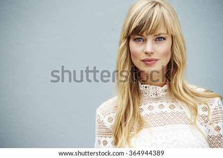 Blue eyed blond model looking at camera - stock photo