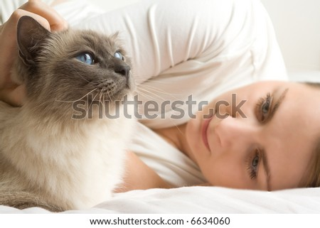 Blue eyed cat with blue eyed  caucasian woman caressing it lying in white bed. - stock photo