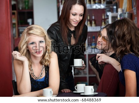 Blue-eyed college girl poses while three friends talk to each other