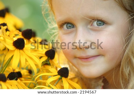 Blue-eyed girl with brown-eyed susans.  Close-up of a beautiful young girl standing next to a batch of flowers. Great symbol of youth, growth, summertime, innocence, etc. - stock photo