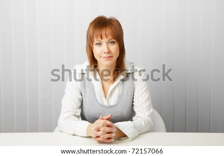 blue-eyed happy attractive young businesswoman in office - stock photo