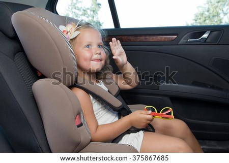 Blue-eyed little girl inside the vehicle waving his hand while sitting in the car seat - stock photo