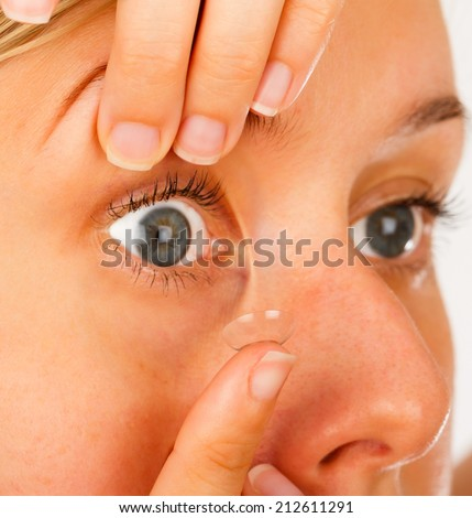 Blue eyed woman applying easily contact lenses. - stock photo