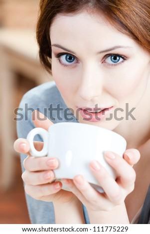Blue-eyed woman with cup of tea has a rest at the restaurant - stock photo