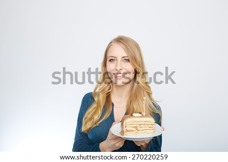 Blue eyes beautiful blond young woman with large chocolate piece of cake happy looking at camera on white background portrait - stock photo