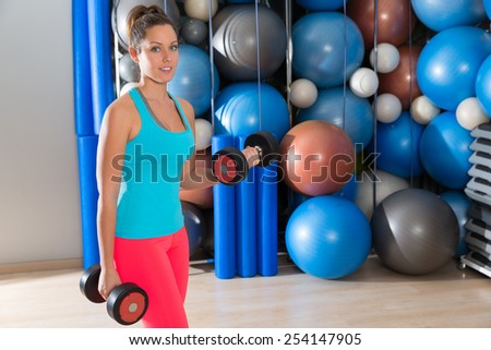 Blue eyes girl at gym weightlifting dumbbells in fitness training - stock photo