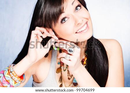 blue eyes girl put earring and smiling portrait studio shot - stock photo