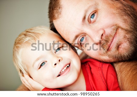 blue eyes happy father and toddler son closeup portrait - shallow depth of field, focus on father eyes - stock photo
