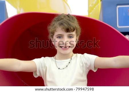 blue eyes indented girl smiling in red playground - stock photo