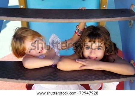 blue eyes little sister girls smiling hide under playground slide stairs - stock photo