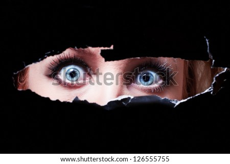Blue eyes of a young woman peeping through a hole - stock photo