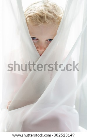 blue eyes of adorable blond child among white curtain filtered desaturated effect - stock photo