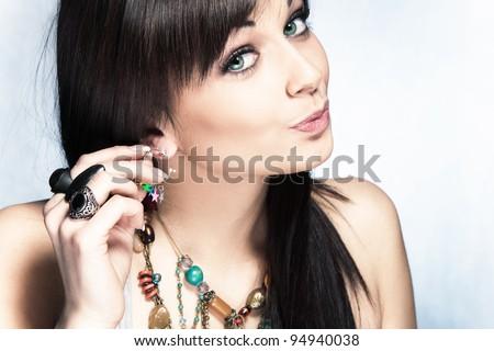 blue eyes woman put on earring, studio shot - stock photo