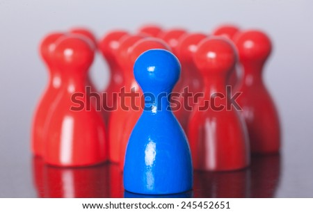 Blue Figure stand in front onf many red Figures . Show a leading position metaphor. - stock photo