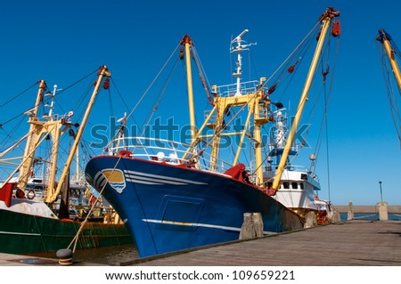 Blue fish boat or trawler in the harbor - stock photo