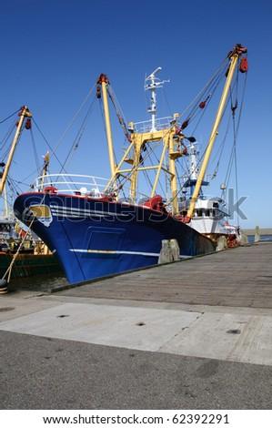 blue fish trawler in the harbor - stock photo