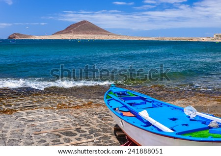 Blue fishing boat on the beach of El Medano village, Tenerife, Canary Islands, Spain - stock photo