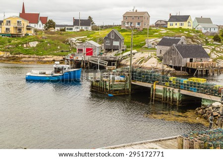 Blue fishing boat returning to harbor at Peggy's Cove Village on coast of Bay of Fundy in Nova Scotia Canada. - stock photo