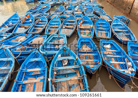Blue fishing boats in the harbor at the Sqala du Port, in Essaouira, Morocco, on the southern Atlantic Coast. Boats are used every day for fishing at sea, the ocean.