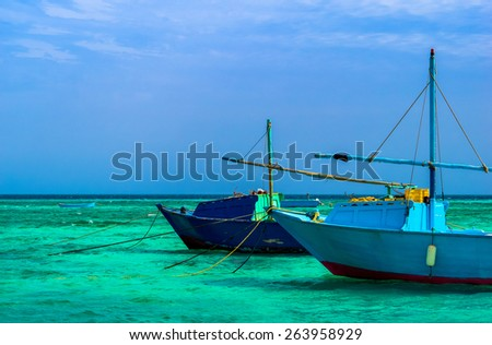 Blue fishing boats on anchored at sea lagoon. Seaside with two fisherman boats in blue colors. - stock photo