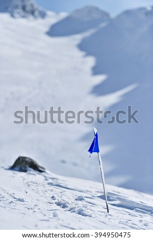 Blue flag blown by the wind on a mountain in winter - stock photo