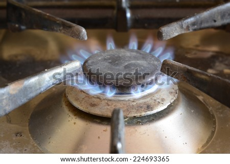 Blue flame on a domestic gas cooker ring. Dirty with food splashes. - stock photo
