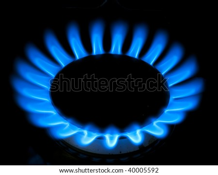 blue flames of gas stove on black background, some parts of stove are visible