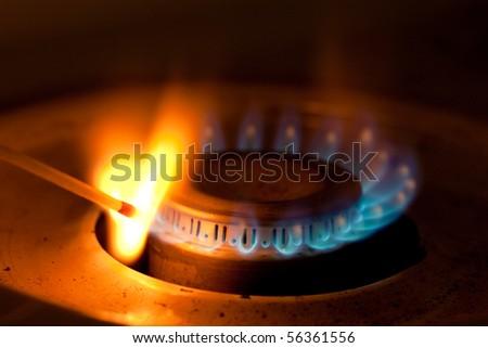 Blue flames of propane burner ignite match - stock photo